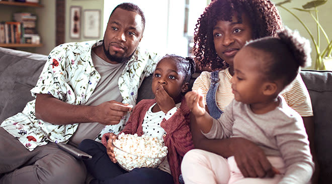 family sits on the couch together while eating popcorn and watching TV.