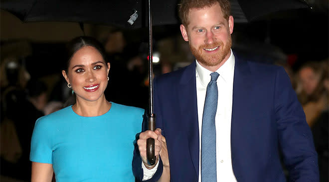 prince harry and meghan markle walking under an umbrella