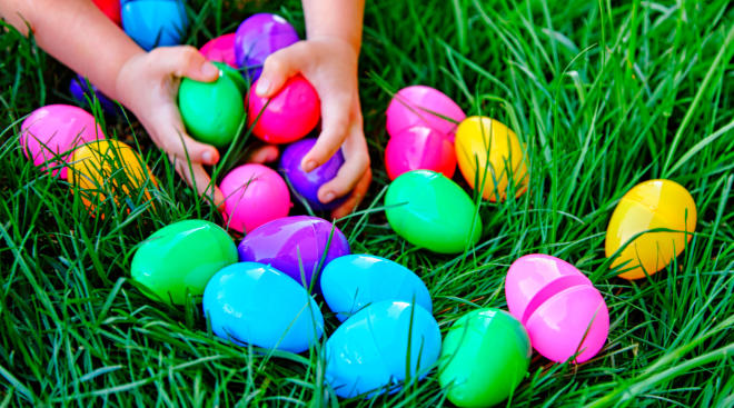 toddler hands grabbing for easter eggs in the grass