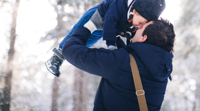 dad lifting up son wearing snow boots in snow