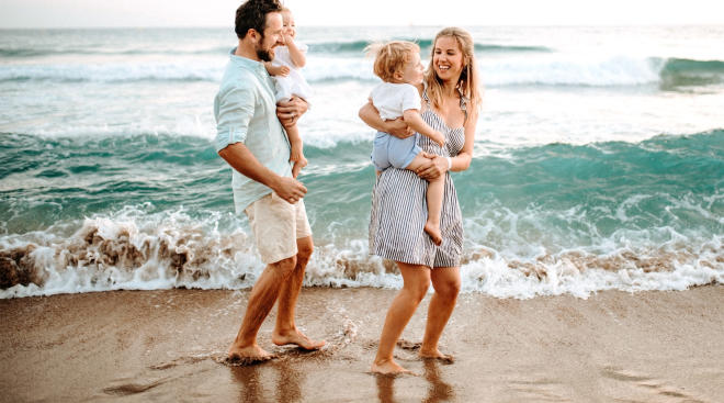 young happy family walking along the beach
