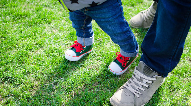 parent helping baby who is wearing shoes walk