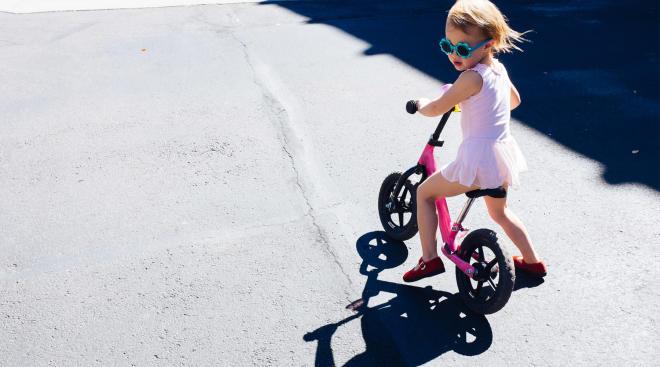 toddler rides pink balance bike