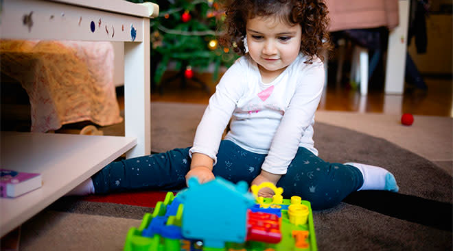 smiling toddler girl with just opened christmas toy