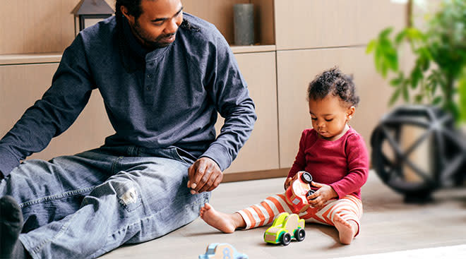 toddler playing with toy cars while dad sits nearby