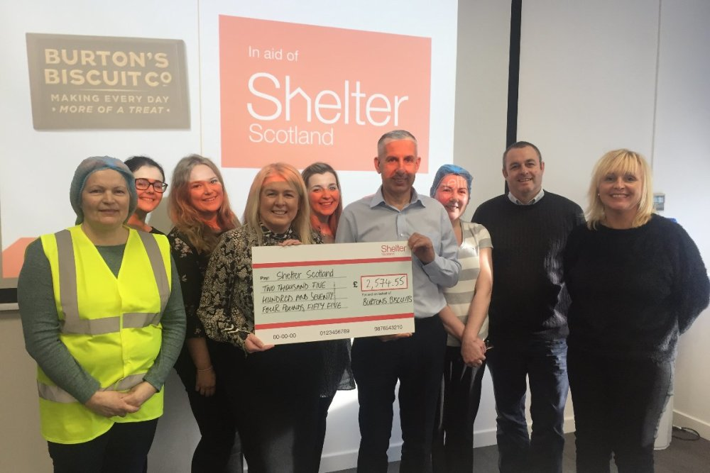 The team at Burtons Biscuits holding a cheque for Shelter Scotland