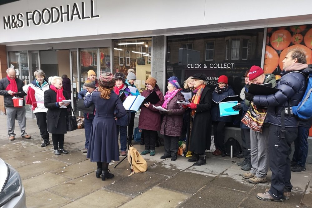 A choir singing outside of Marks and Spencer Food Hall in Edinburgh