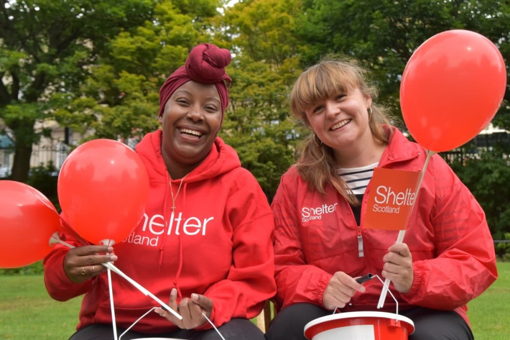 Two woman with Shelter Scotland hoodies on holding balloons and a fundraising bucket