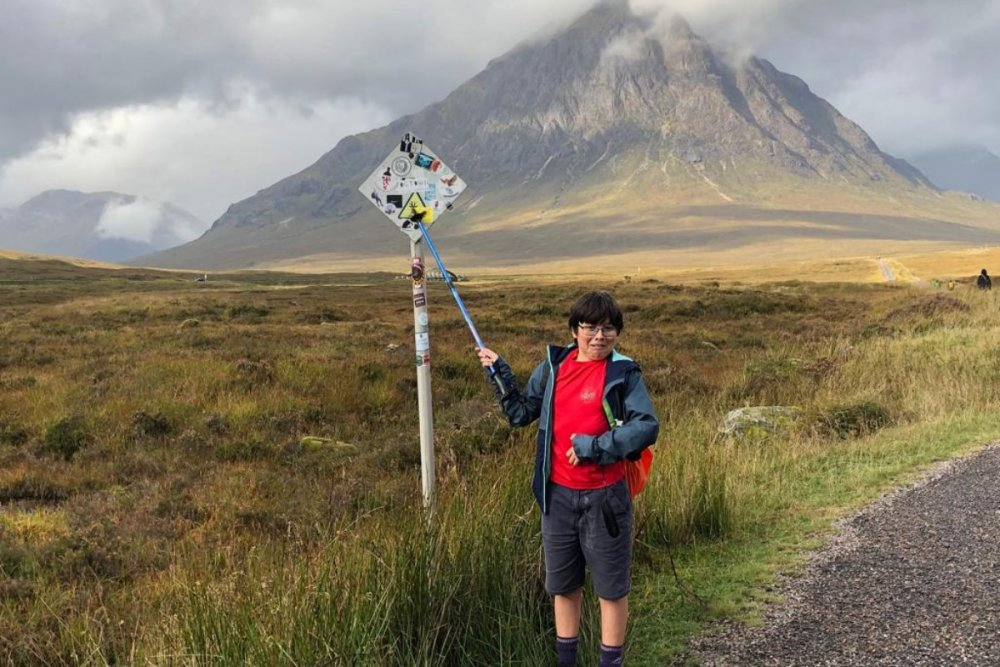 Keir standing in front of a sign with a Munro shrouded in cloud behind him.
