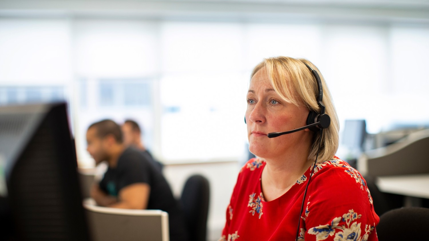 A Shelter helpline adviser on a call, wearing a headset