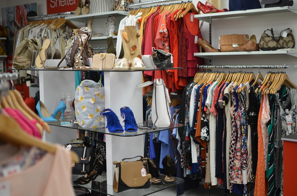 Rows of clothes and racks of accessories in a Shelter charity shop