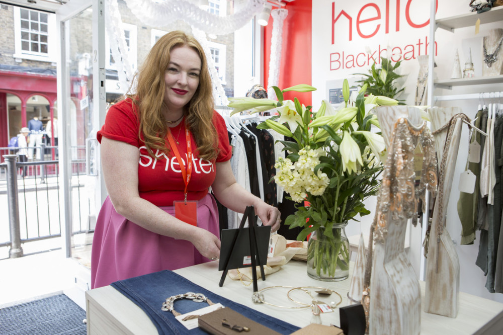 A smiling shop volunteer arranges a colourful display of clothes at the Shelter Boutique in Blackheath