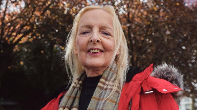 便士穿着一件红色外套和围巾,站在一个秋季公园
