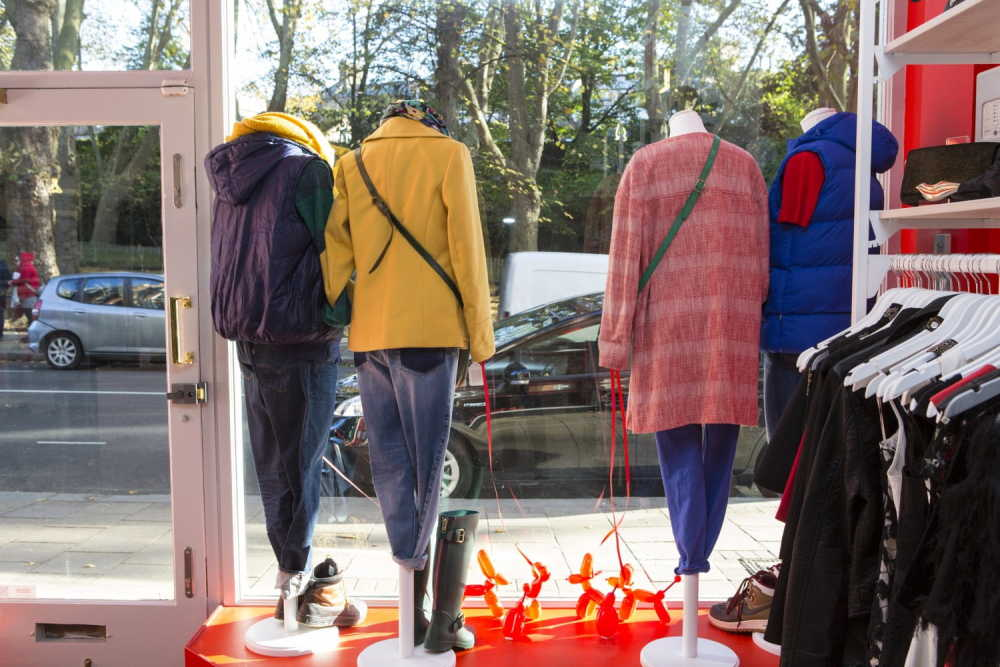 Mannequins wearing a colourful selection of clothes in the window of a Shelter shop