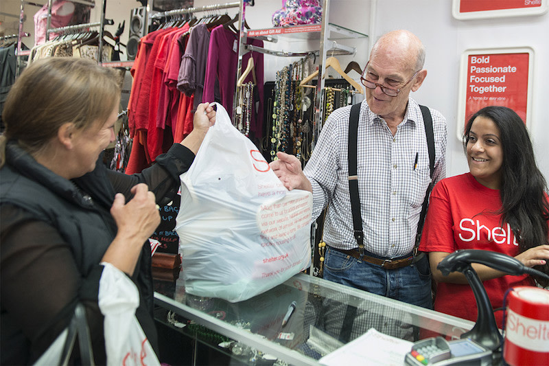 A volunteer serving a customer in a Shelter charity shop