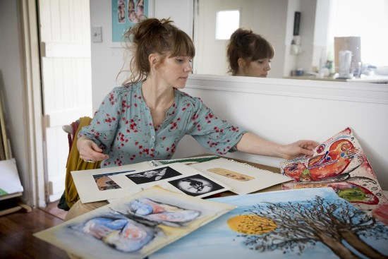 A photo of Lauren looking through artwork in her new social home.