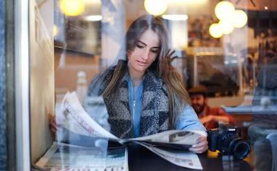 A woman reads a newspaper in a cafe. Photo by Keenan Constance — https://unsplash.com/photos/F7n6gixbJK0