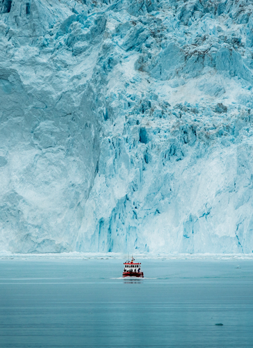 web A small passenger boat in front of the huge glacier wall at the Eqi glacier in Greenland