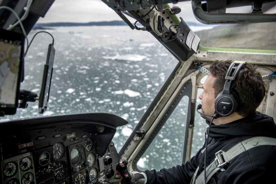 An Air Greenland Bell 212 helicopter pilot over the Ilulissat ice fjord in Greenland