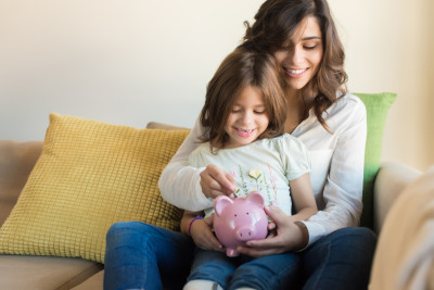 Woman and Little Girl with a Piggy Bank