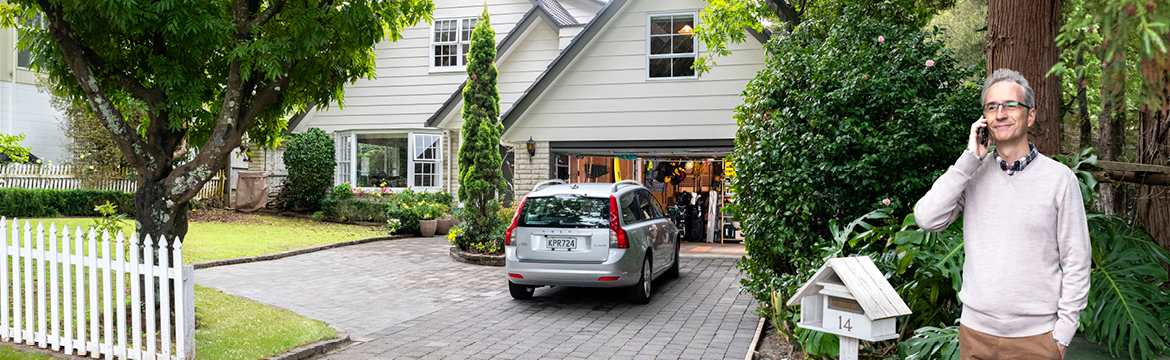 A house with a car parked outside the open garage and a man in the right corner on the phone