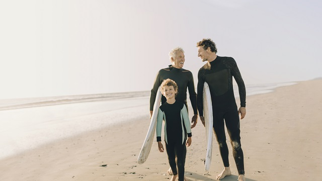 A grand-dad, dad and son walking on the beach in wet-suits with surfboards