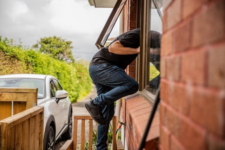 Man getting through window
