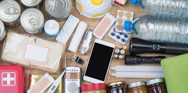 Image of typical emergency kit items, including water, torches, canned food, medication and a radio