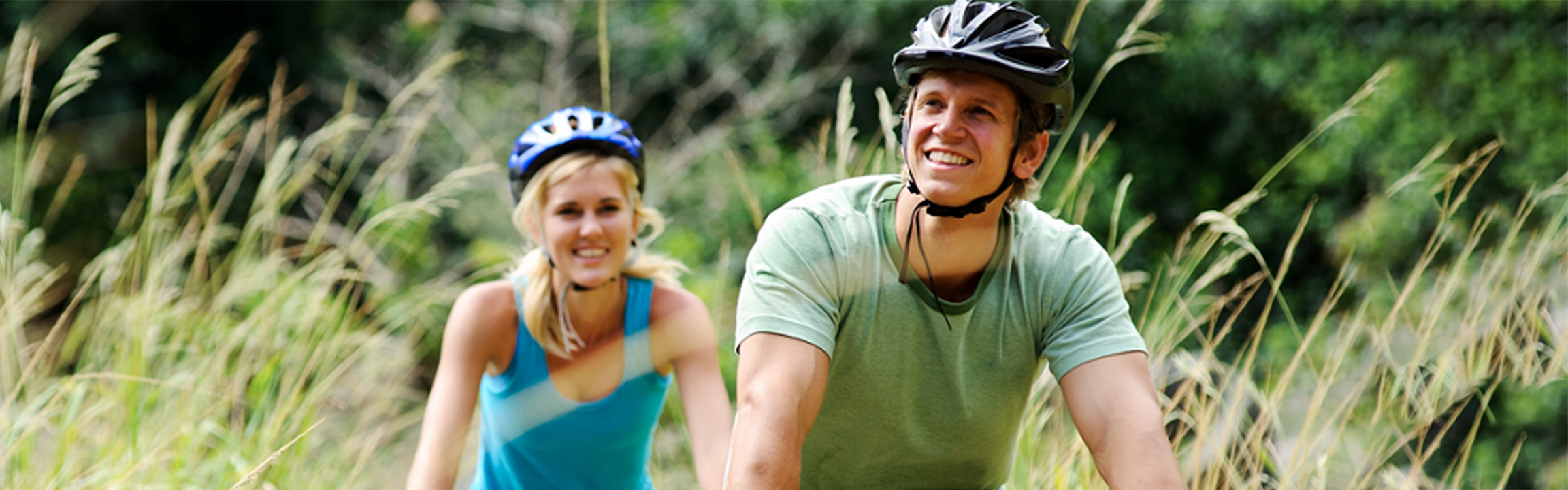 A man and a woman smile gleefully as they ride their bicycles in a field.