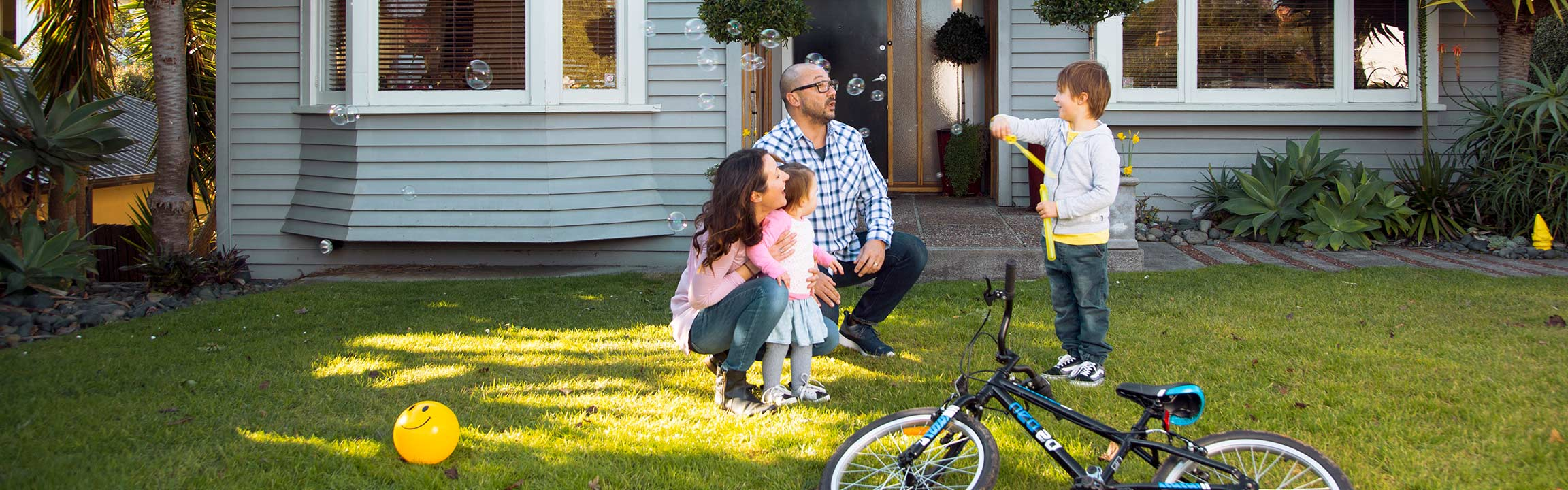 A family playing outside their house in the front yard with a bike, ball and blowing bubbles