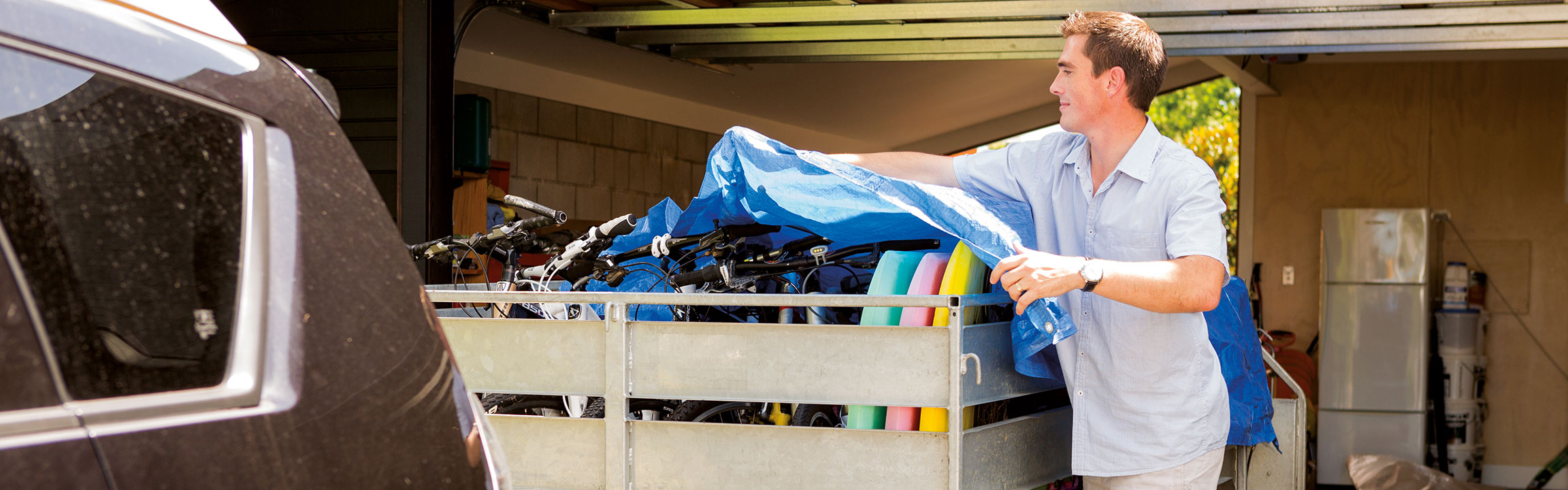 A man covering his trailer holding bikes and body boards