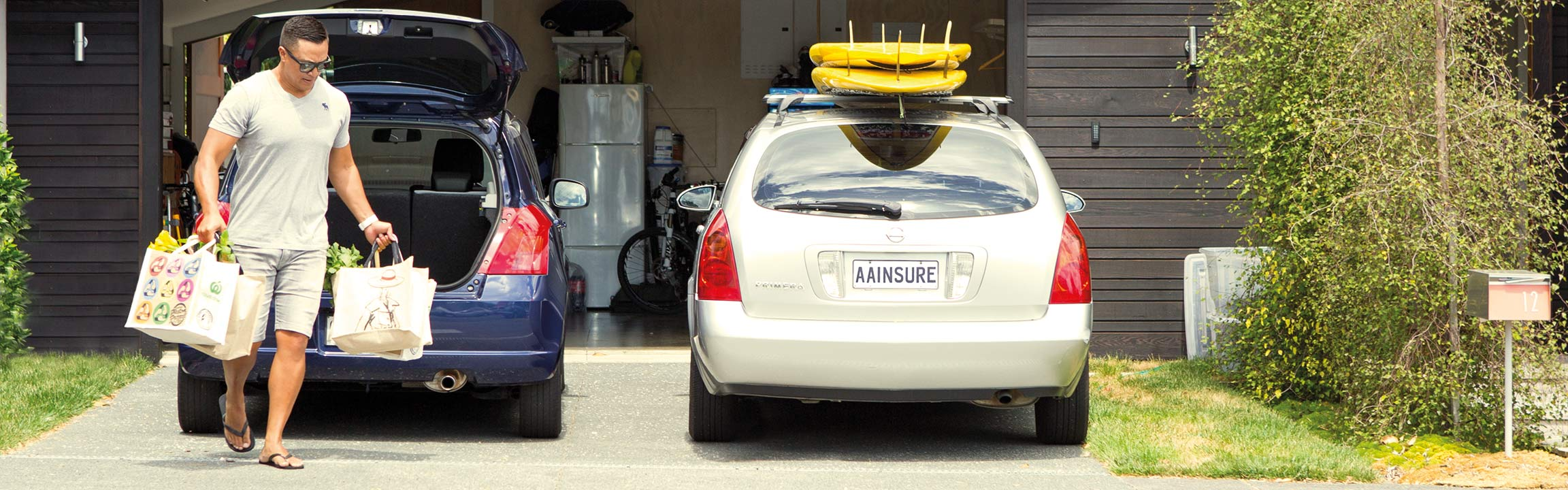 A man carrying groceries out of his car parked at his home outside the garage