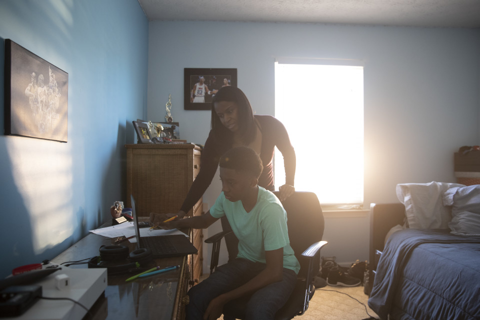 Tonia helps her son with online school work at home