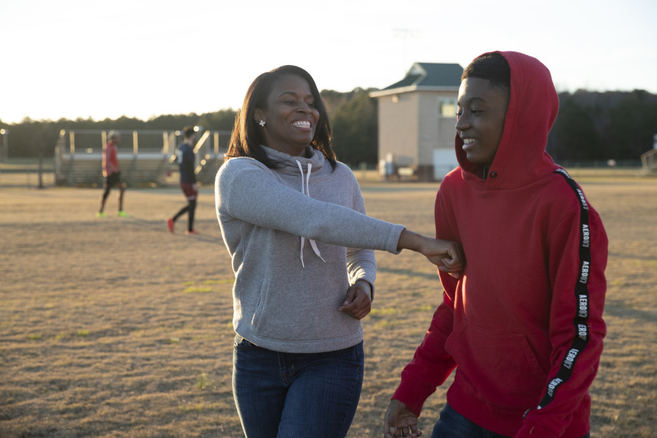 Tonia and her son joke as they walk off the football field