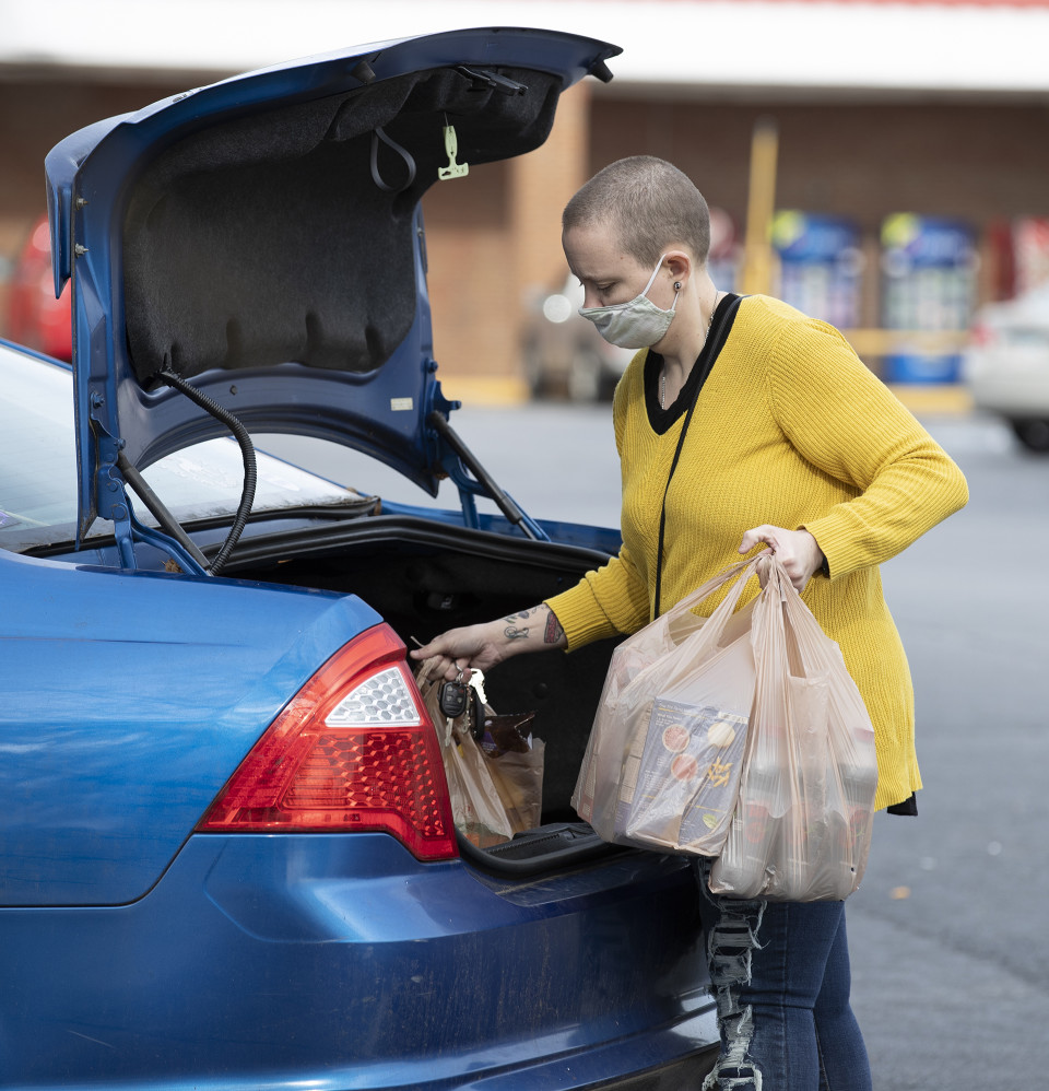 Ashley loads groceries into her car at the supermarket