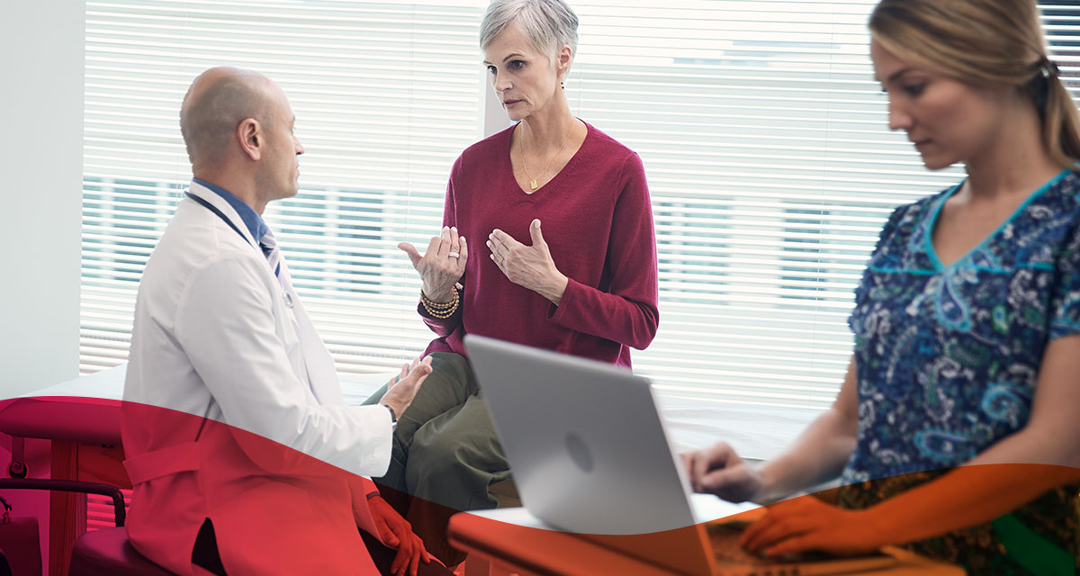 Patient and provider engage in conversation while nurse enters data