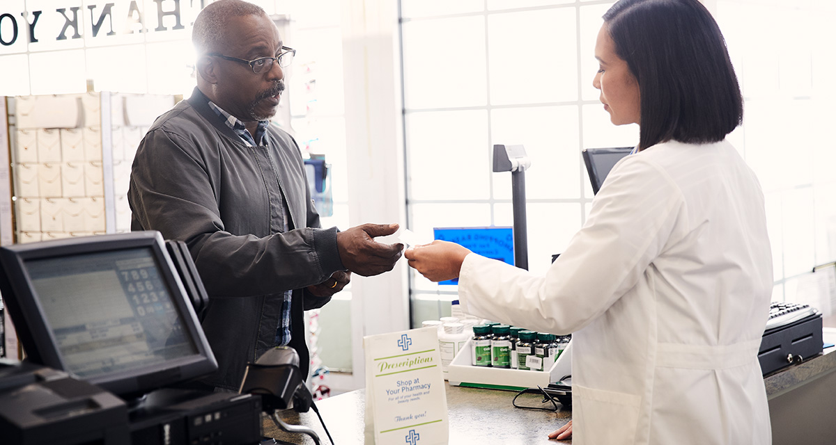 A man at a pharmacy paying for his prescription