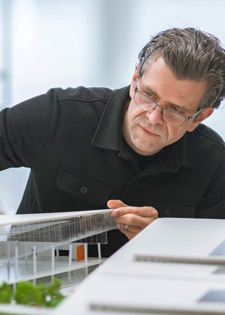 An architect interacts with a model of the CoverMyMeds campus.