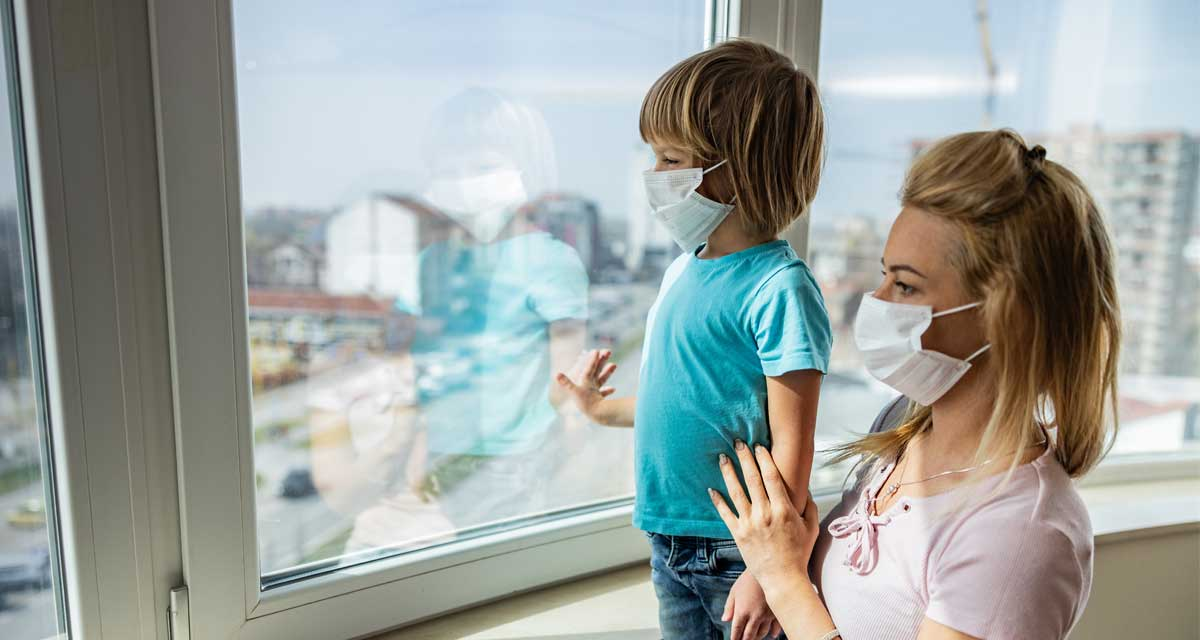 A mother and son wearing face coverings looking out a hospital window