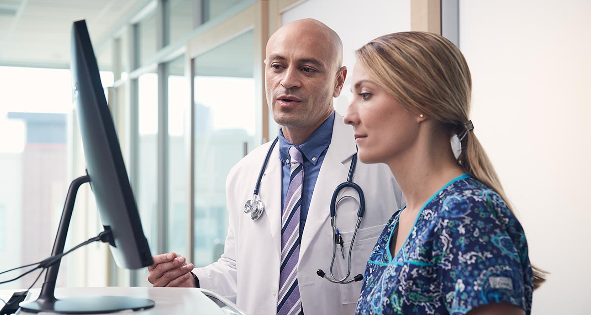 Doctor and nurse meet in front of a computer
