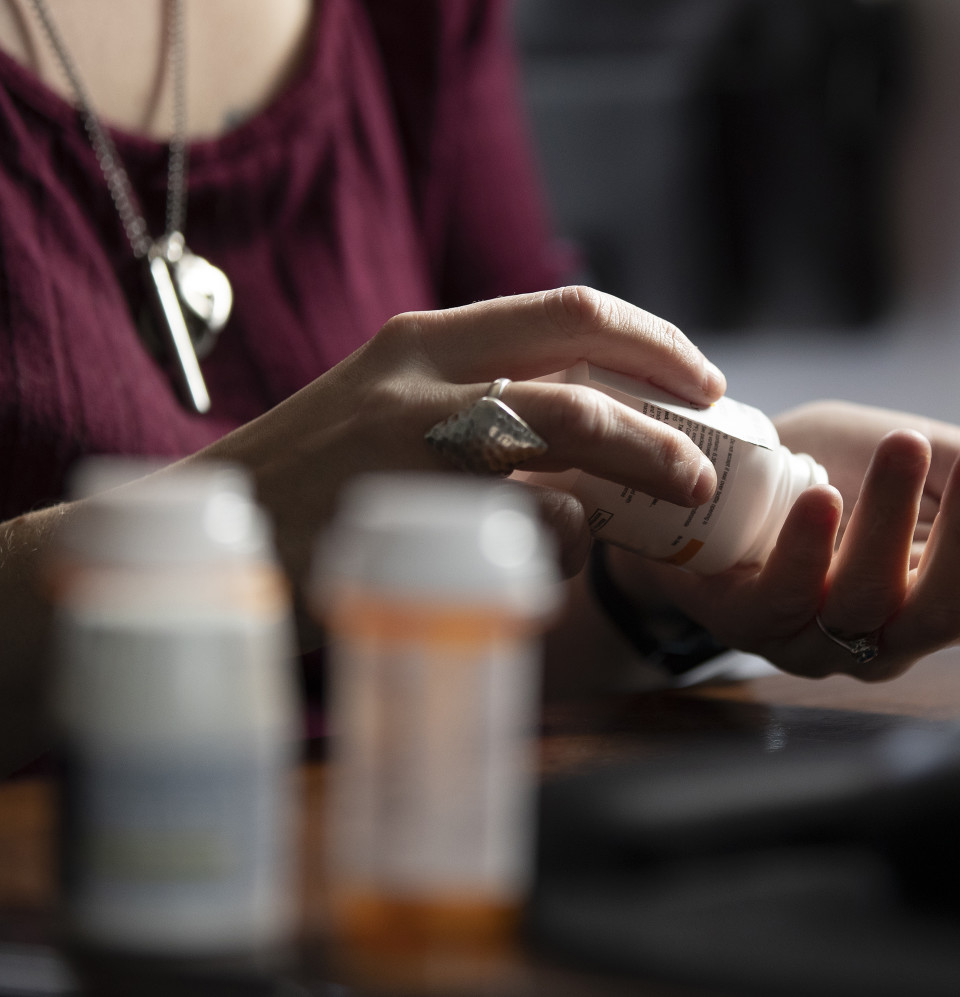 Patient shaking pills out of a bottle into her hand
