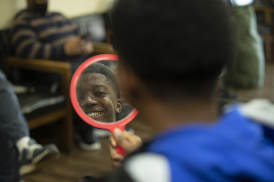 Tonia's son looks into a mirror at the barber shop