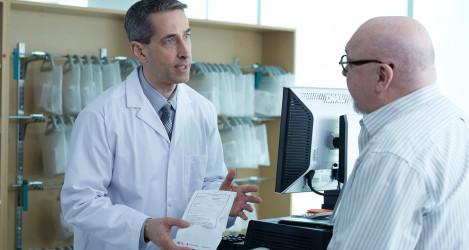 Pharmacist discusses prescription with patient.
