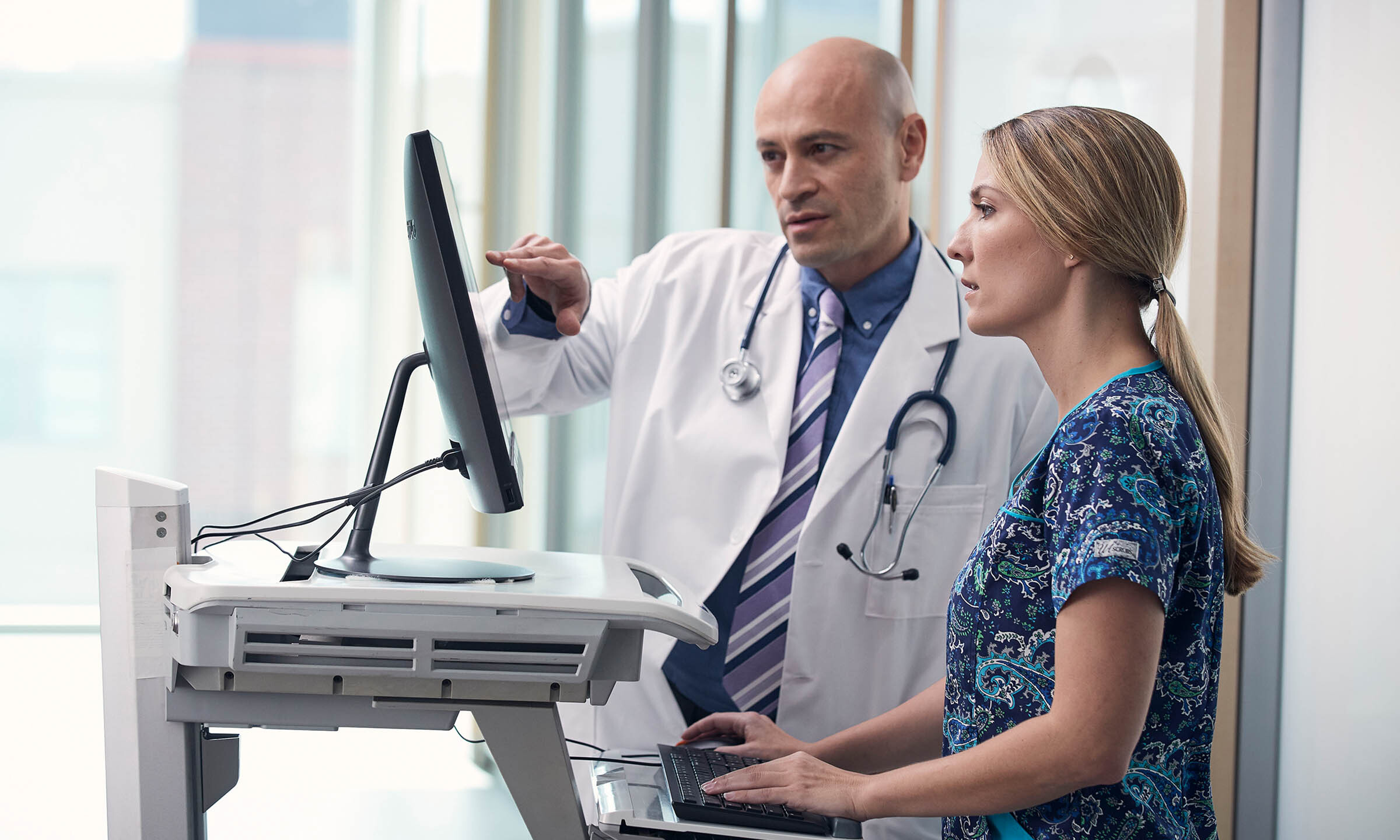 Providers discuss treatment options for a patient in front of a computer.
