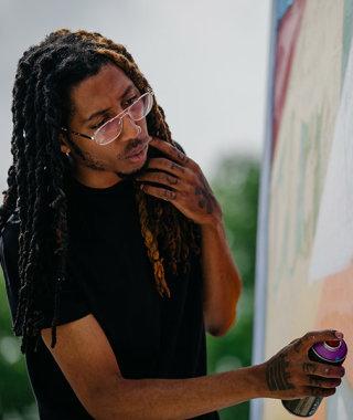 Columbus artist Hakim Callwood working on his Black Lives Matter mural