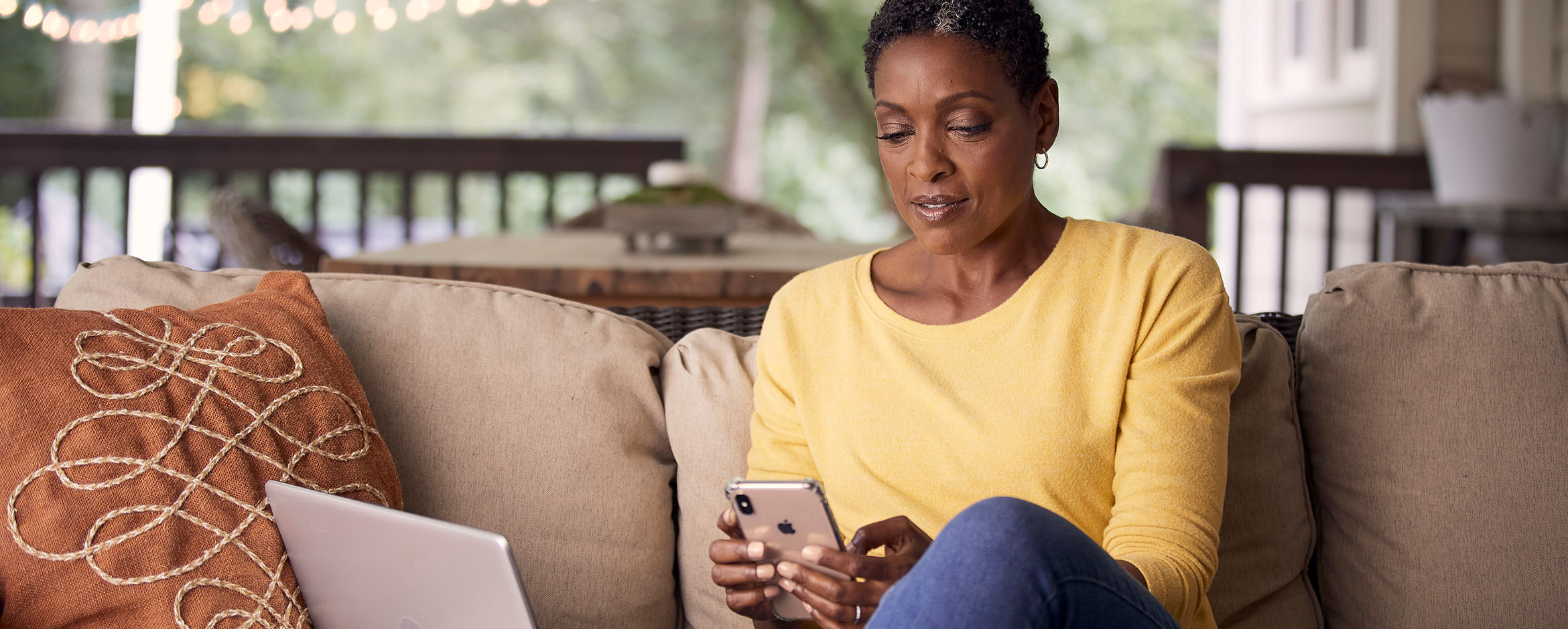 A woman sits on her sofa while looking at a medical app on her smartphone.