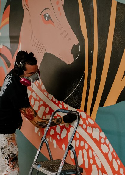 Paul works on his mural at the CoverMyMeds campus.
