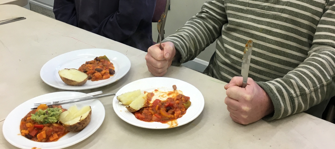 Plates of food with someone holding a knife and fork