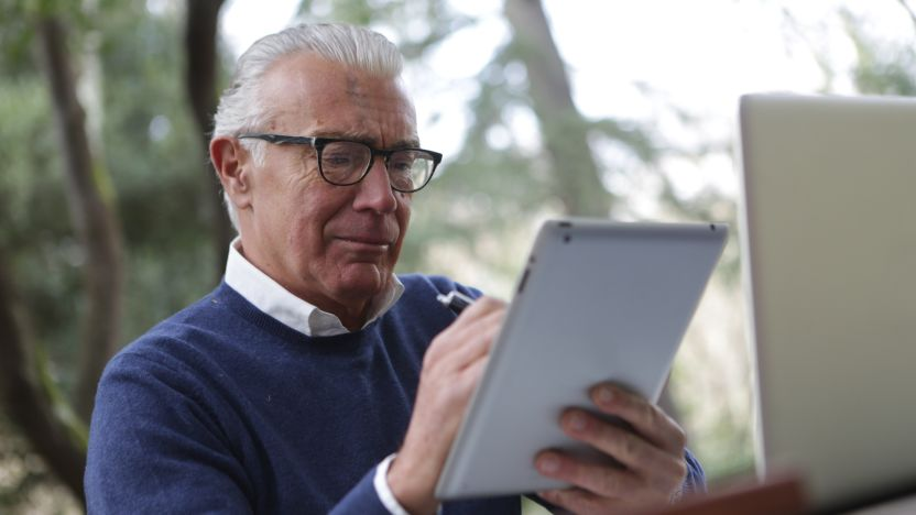 Older man in blue sweater with a lap top and using a tablet