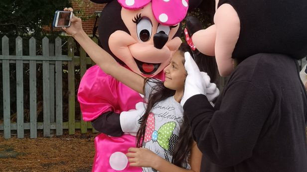 Mickey and Minnie Mouse taking a photo with a child